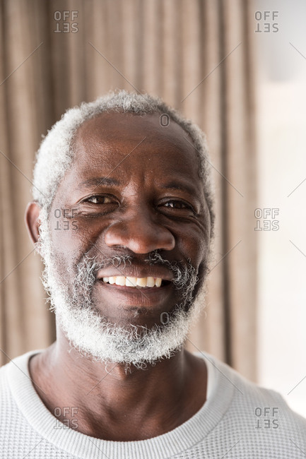 Portrait of a senior African American man spending time at home, social distancing and self isolation in quarantine lockdown during coronavirus covid 19 epidemic, looking at camera and smiling