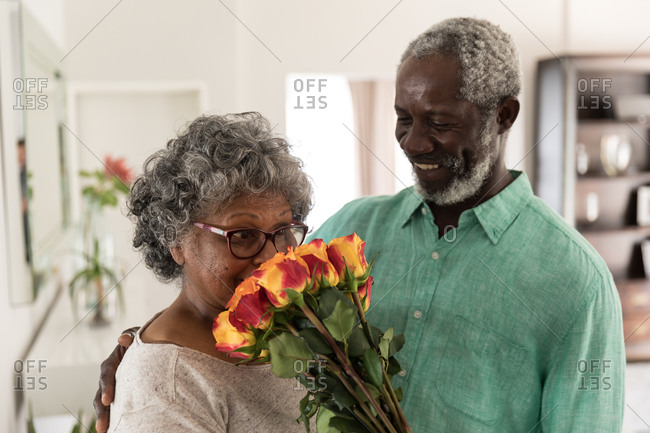 A senior African American couple spending time at home together, social distancing and self isolation in quarantine lockdown during coronavirus covid 19 epidemic, the man holding a bouquet of flowers, smiling and giving them to the woman