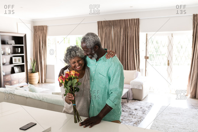 A senior African American couple spending time at home together, social distancing and self isolation in quarantine lockdown during coronavirus covid 19 epidemic, embracing and smiling, the woman holding a bouquet of flowers