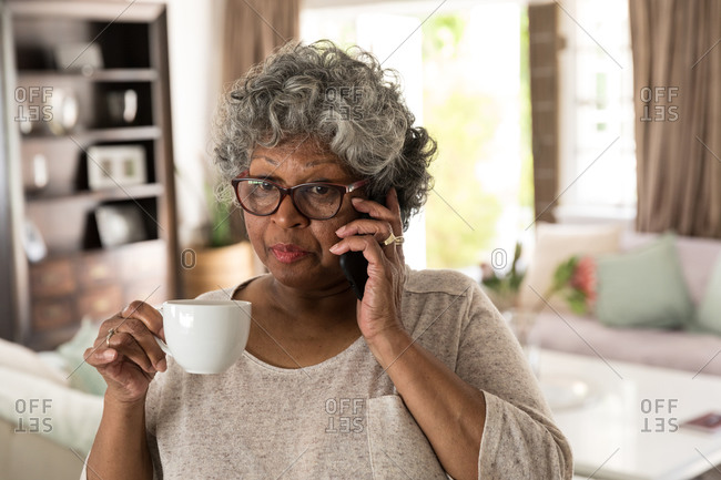 A senior African American woman spending time at home, social distancing and self isolation in quarantine lockdown during coronavirus covid 19 epidemic, talking on a smartphone and holding a cup