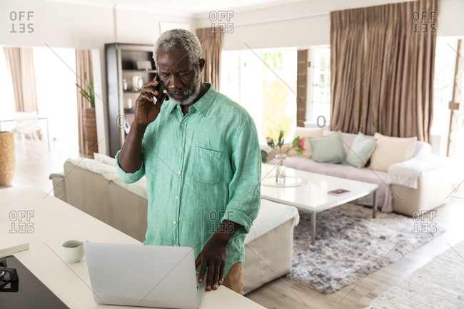 A senior African American man spending time at home, social distancing and self isolation in quarantine lockdown during coronavirus covid 19 epidemic, talking on a smartphone and using a laptop