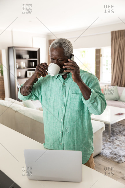 A senior African American man spending time at home, social distancing and self isolation in quarantine lockdown during coronavirus covid 19 epidemic, talking on a smartphone and drinking coffee