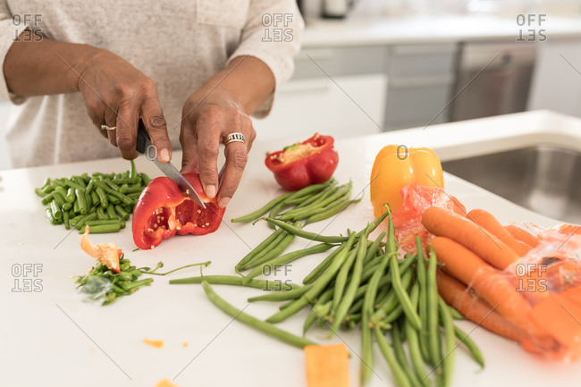 Close up mid section of a senior African American woman spending time at home, social distancing and self isolation in quarantine lockdown during coronavirus covid 19 epidemic, chopping vegetables on a chopping board