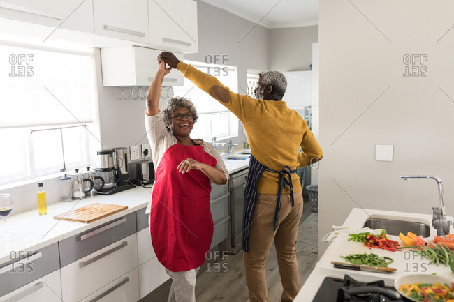 A senior African American couple spending time at home together, social distancing and self isolation in quarantine lockdown during coronavirus covid 19 epidemic, dancing in the kitchen