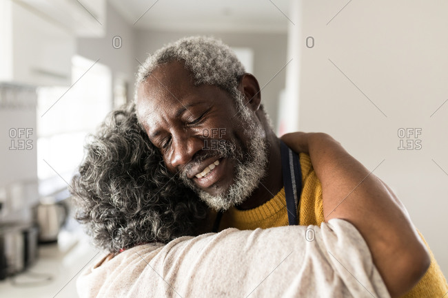 A senior African American couple spending time at home together, social distancing and self isolation in quarantine lockdown during coronavirus covid 19 epidemic, embracing, smiling