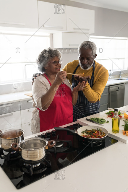A senior African American couple spending time at home together, social distancing and self isolation in quarantine lockdown during coronavirus covid 19 epidemic, standing in the kitchen preparing food
