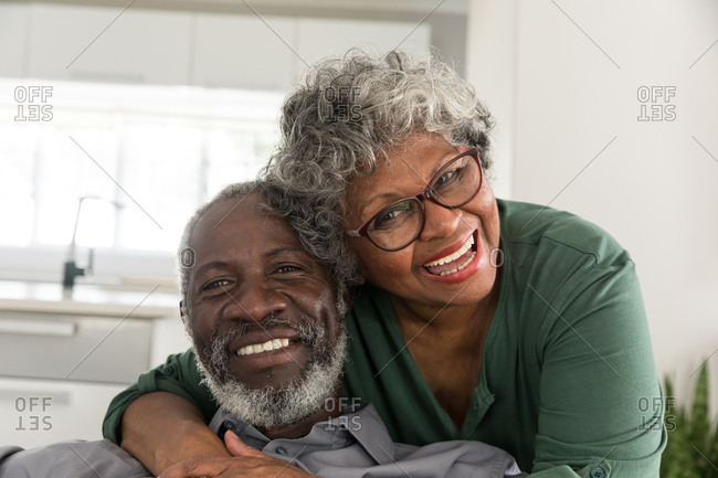 Portrait of a senior African American couple spending time at home together, social distancing and self isolation in quarantine lockdown during coronavirus covid 19 epidemic, looking at camera, smiling, embracing