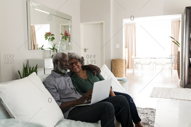 A senior African American couple spending time at home together, social distancing and self isolation in quarantine lockdown during coronavirus covid 19 epidemic, sitting on a sofa, embracing, using a laptop
