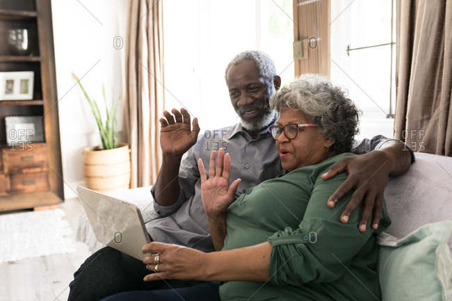 A senior African American couple spending time at home together, social distancing and self isolation in quarantine lockdown during coronavirus covid 19 epidemic, using a tablet, making a video call to friends or relatives, waving
