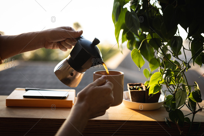 Mid section of a Caucasian woman spending time at home self isolating and social distancing in quarantine lockdown during coronavirus covid 19 epidemic, pouring coffee from a moka pot.