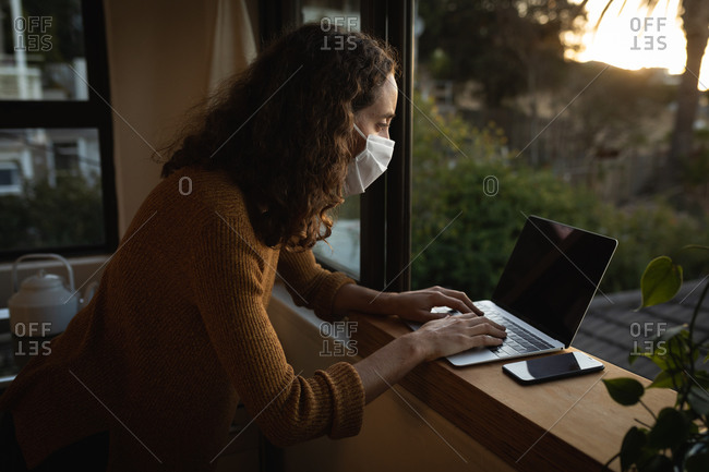 Caucasian woman spending time at home self isolating and social distancing in quarantine lockdown during coronavirus covid 19 epidemic, wearing a face mask against covid19 coronavirus, sitting by a window and working using her laptop computer.