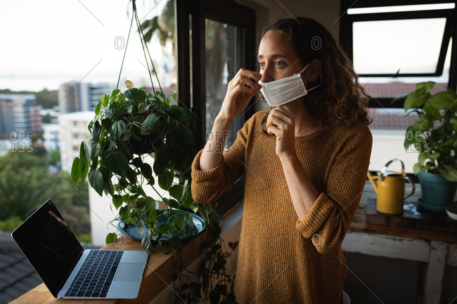 Caucasian woman spending time at home self isolating and social distancing in quarantine lockdown during coronavirus covid 19 epidemic, putting on a face mask against covid19 coronavirus, standing by a window and preparing to work using her laptop computer.