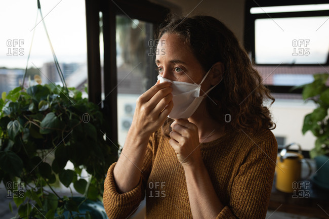 Caucasian woman spending time at home self isolating and social distancing in quarantine lockdown during coronavirus covid 19 epidemic, putting on a face mask against covid19 coronavirus, standing by a window.