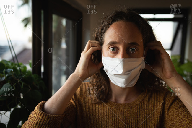 Portrait of a Caucasian woman spending time at home self isolating and social distancing in quarantine lockdown during coronavirus covid 19 epidemic, putting on a face mask against covid19 coronavirus, looking straight into a camera.