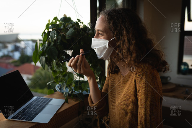 Caucasian woman spending time at home self isolating and social distancing in quarantine lockdown during coronavirus covid 19 epidemic, wearing a face mask against covid19 coronavirus, standing by a window, talking on her smartphone and using a laptop computer.