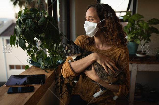 Caucasian woman spending time at home self isolating and social distancing in quarantine lockdown during coronavirus covid 19 epidemic, wearing a face mask against covid19 coronavirus, standing by a window and holding her cat.