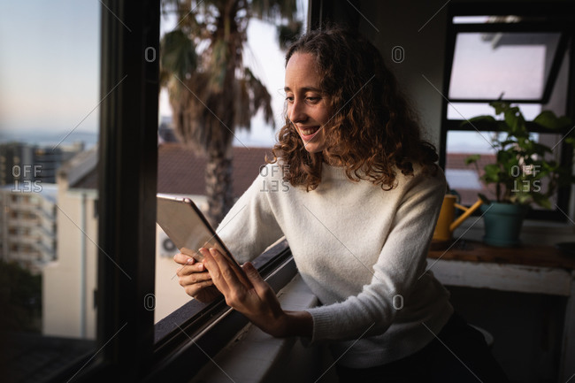 Caucasian woman spending time at home self isolating and social distancing in quarantine lockdown during coronavirus covid 19 epidemic, sitting by the window and smiling while using tablet.