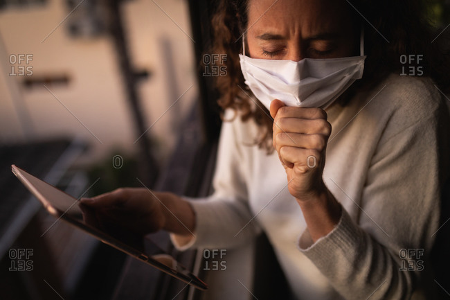 Caucasian woman spending time at home self isolating and social distancing in quarantine lockdown during coronavirus covid 19 epidemic, wearing a face mask against covid19 coronavirus, standing by a window, using her tablet and covering her mouth while coughing.