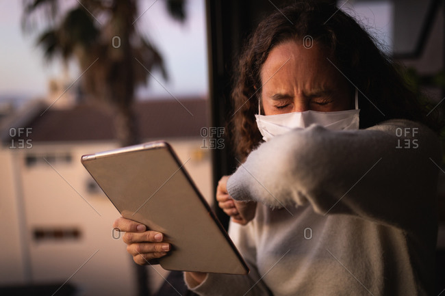 Caucasian woman wearing a face mask and coughing into her arm while at home during the Covid-19 quarantine lockdown using a tablet computer by window