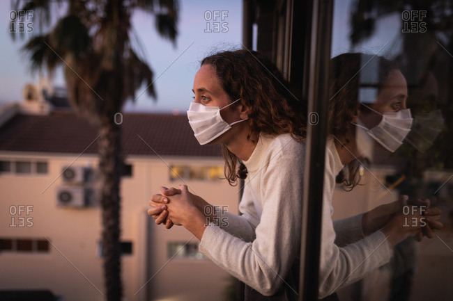 Caucasian woman spending time at home self isolating and social distancing in quarantine lockdown during coronavirus covid 19 epidemic, wearing a face mask against covid19 coronavirus, looking through the window.
