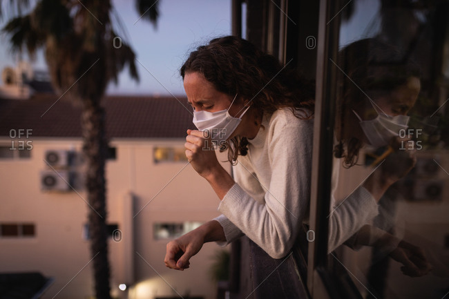 Caucasian woman spending time at home self isolating and social distancing in quarantine lockdown during coronavirus covid 19 epidemic, wearing a face mask against covid19 coronavirus, looking through the window and coughing.