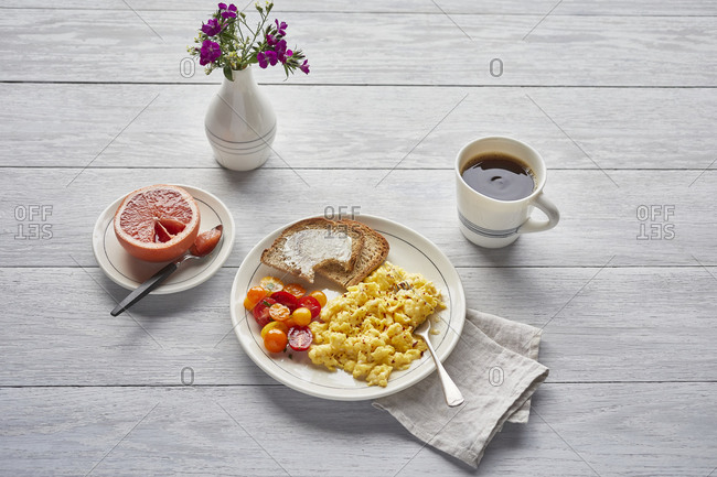 Eggs with toast and tomatoes, coffee, grapefruit