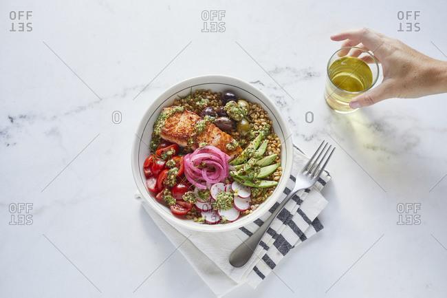 Grain bowl with salmon, avocado, tomato, radish, olives