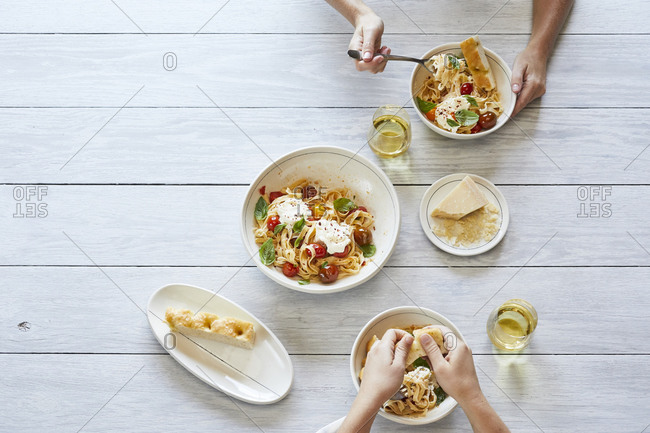 Pasta with tomato and ricotta on a table with bread and wine