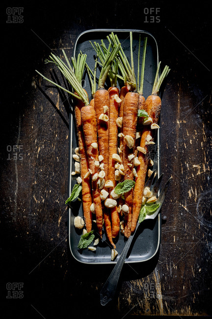 Carrots on black plate with marcona almonds