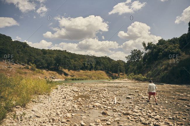 Solo man walking through the river