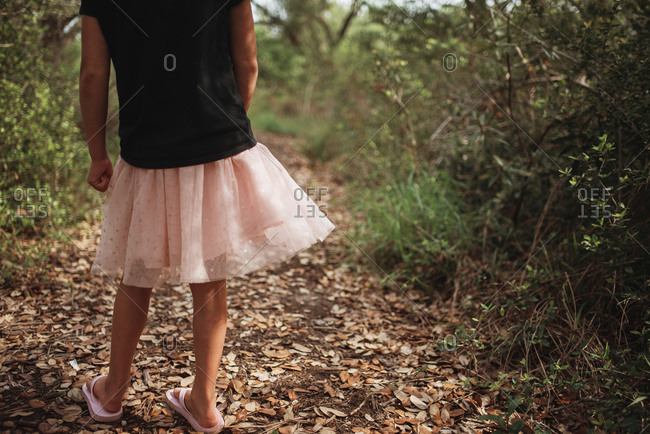 Little girl in frilly skirt on a walk in the forest