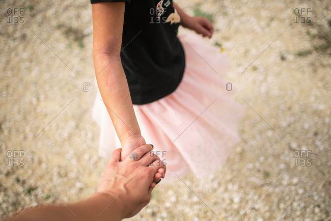 Little girl in frilly skirt on a walk on a rocky path with mom