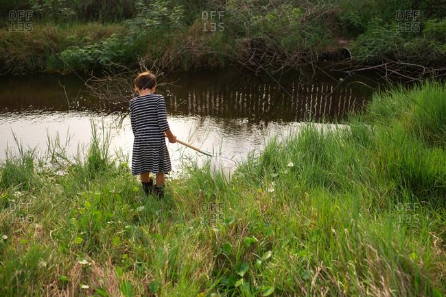 Little girl fishing in creek