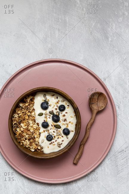 Bowl of muesli and blueberries on yogurt, wooden teaspoon