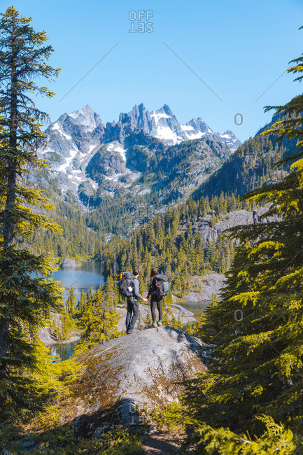 Hikers enjoying view on rock, Alpine Lakes Wilderness, Washington, USA