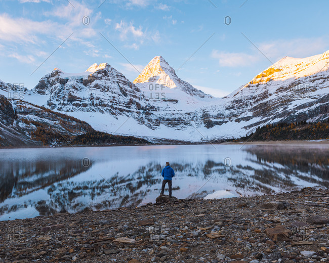 A man taking in the view across a lake to the panoramic view of Mount Assiniboine, Great Divide, Canadian Rockies, Alberta, Canada