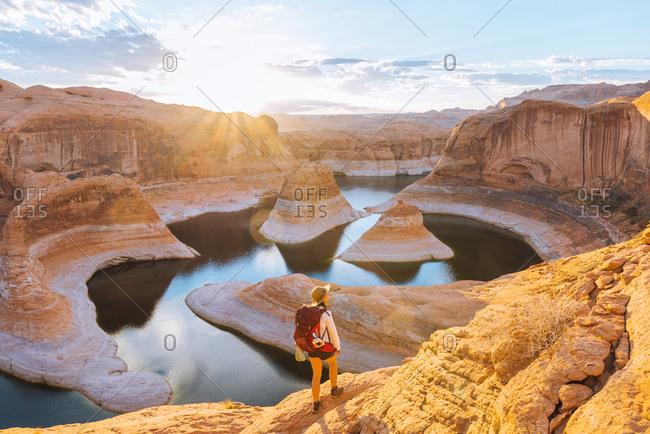 Backpacker at sunrise, Reflection Canyon, Lake Powell, Utah, US
