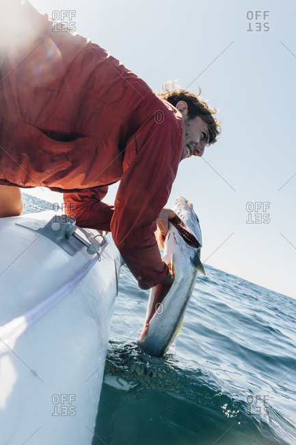 Close up of fisherman pulling fish out of ocean.
