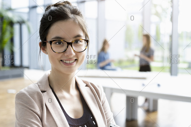 Portrait of young businesswoman with dark brown hair wearing glasses.