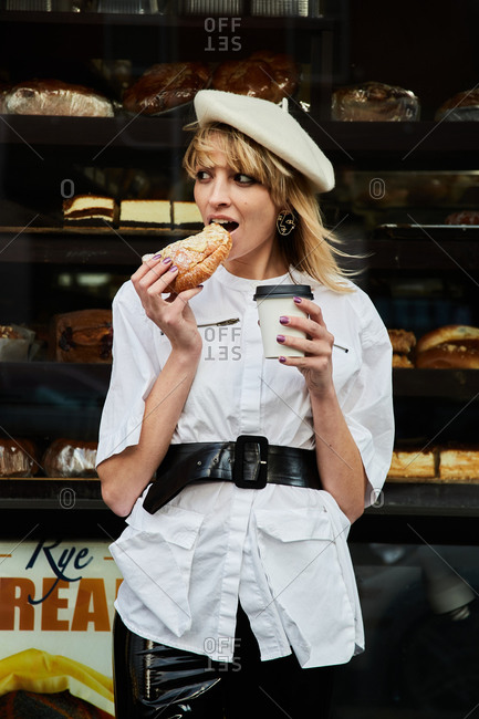 Pretty blonde woman having a pastry snack on the street, wearing a chic black and white outfit and beret.