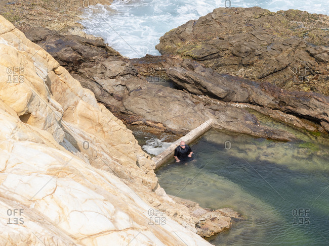 High angle view of senior man going for a swim at a rock pool in Bermagui, Australia.