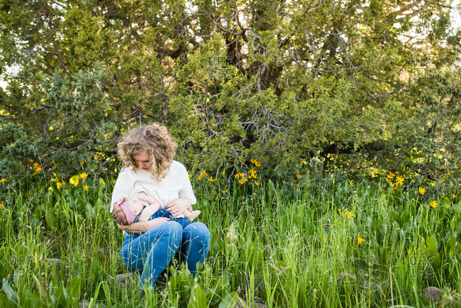 Mom breastfeeding baby while sitting in a meadow