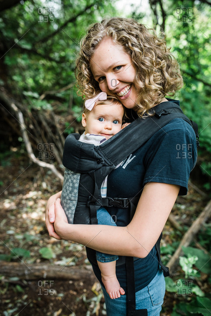 Portrait of mom carrying baby girl while hiking