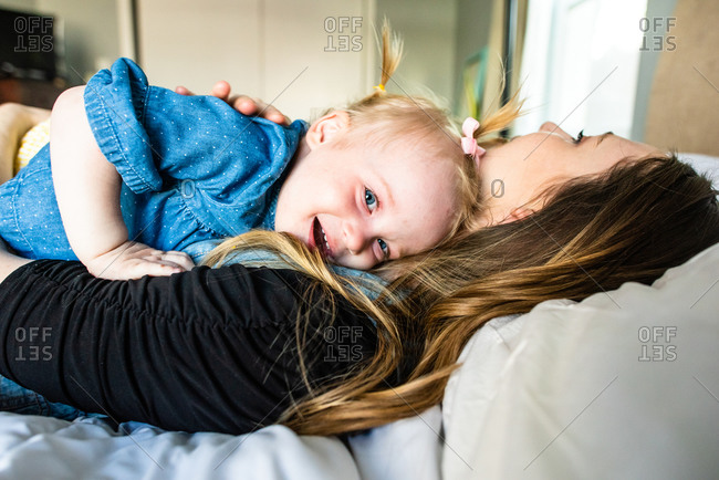 Mom and daughter cuddle on a bed