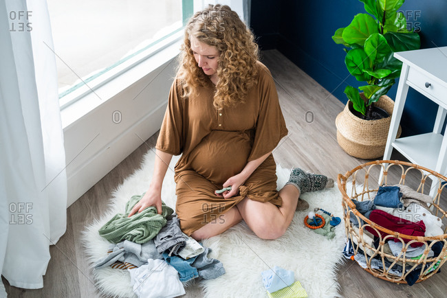 Expectant mother organizing laundry on the floor