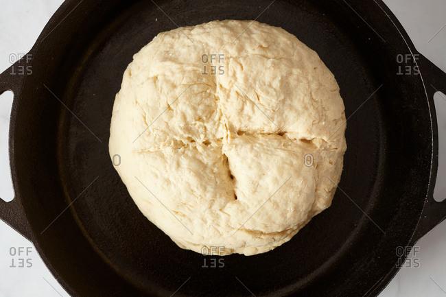 Scored raw Irish soda bread in cast iron skillet ready for the oven