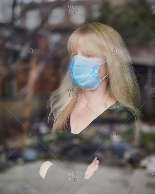 Woman wearing personal protective mask at window looking outside