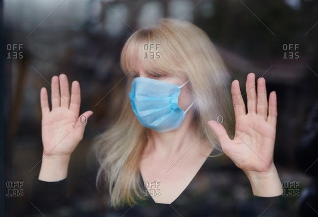 Woman wearing mask at window looking outside who is staying home due to the covid-19 virus