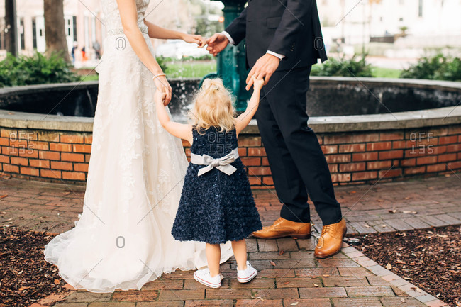 Bride and groom holding little girls hand by fountain