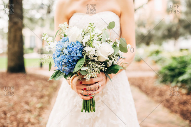 Bride holding a bouquet of blue hydrangeas and white roses